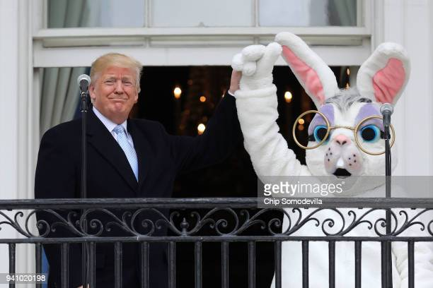 S President Donald Trump lifts the hand of a person in an Easter Bunny costume on the Truman Balcony during the 140th annual Easter Egg Roll on the...