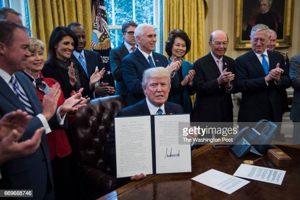 President Donald Trump lifts the order after signing an Executive Order entitled Comprehensive Plan for Reorganizing the Executive Branch in the Oval...
