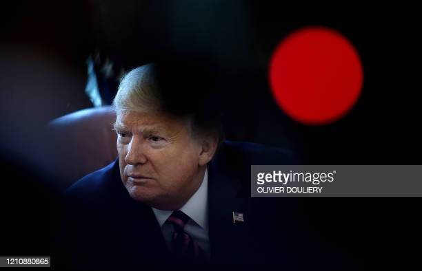 US President Donald Trump lisstens to reporters questions after signing the Paycheck Protection Program and Health Care Enhancement Act in the Oval...