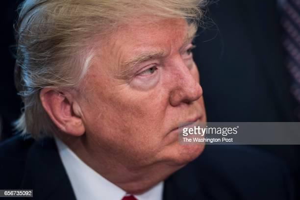 President Donald Trump listens after signing a bill to increase NASA's budget to $195 billion and directs the agency to focus human exploration of...