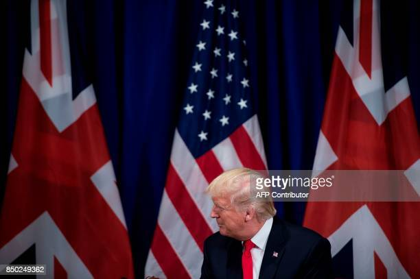 US President Donald Trump listens as Britain's Prime Minister Theresa May speaks before a a meeting at the Palace Hotel in New York on the sidelines...