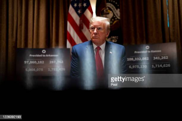 S President Donald Trump listens as he attends a meeting with the Arkansas Governor Asa Hutchinson and Kansas Governor Laura Kelly in the Cabinet...