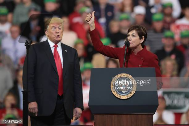 S President Donald Trump listens as Iowa Gov Kim Reynolds speaks during a campaign rally at the MidAmerica Center on October 9 2018 in Council Bluffs...