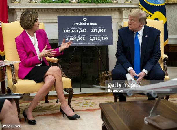 US President Donald Trump listens as Kim Reynolds governor of Iowa left speaks during a meeting in the Oval Office of the White House in Washington...