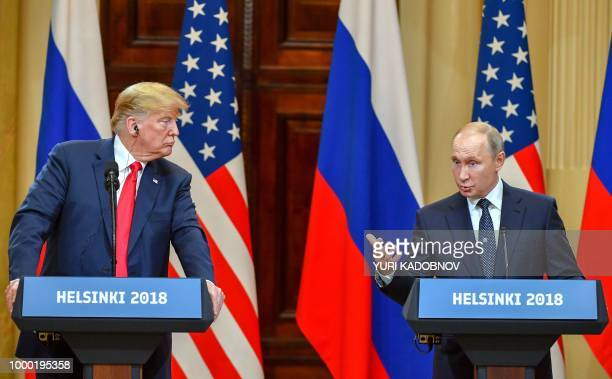 US President Donald Trump listens as Russia's President Vladimir Putin speaks during a joint press conference after a meeting at the Presidential...