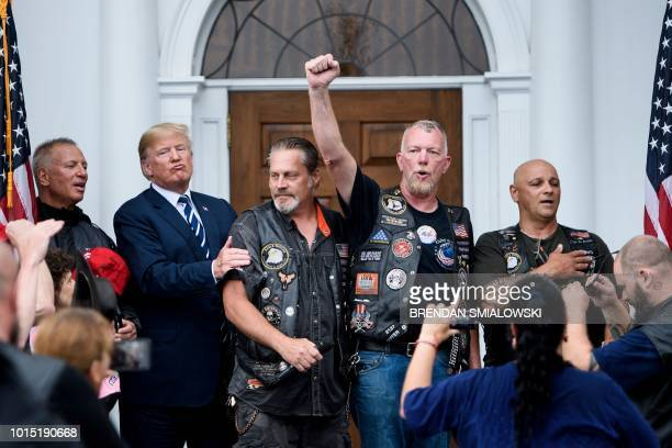 US President Donald Trump listens as supporters cheer following the pledge of allegiance during a Bikers for Trump event at the Trump National Golf...