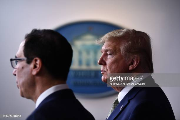 US President Donald Trump listens as Treasury Secretary Steven Mnuchin speaks during the daily press briefing on the Coronavirus pandemic situation...