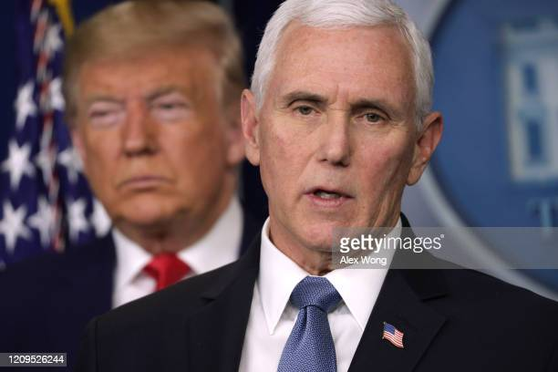 S President Donald Trump listens as Vice President Mike Pence speaks during a news conference at the James Brady Press Briefing Room at the White...