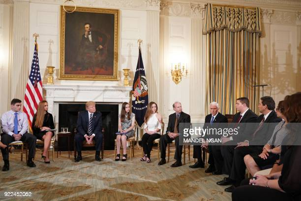US President Donald Trump listens as Vice President Mike Pence speaks during a listening session on gun violence with teachers and students in the...