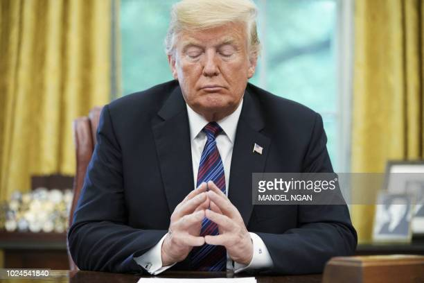 President Donald Trump listens during a phone conversation with Mexico's President Enrique Pena Nieto on trade in the Oval Office of the White House...