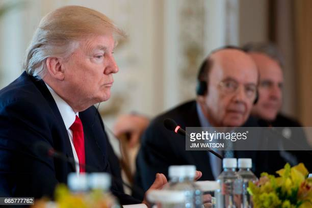 US President Donald Trump listens during an expanded bilateral meeting with Chinese President Xi Jinping at the MaraLago estate in West Palm Beach...