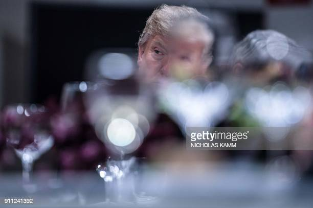 President Donald Trump listens to a speaker during dinner with European business leaders at the World Economic Forum in Davos on January 25 2018 /...