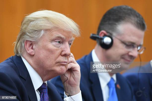 US President Donald Trump listens to a translation during a meeting with Vietnamese Prime Minister Nguyen Xuan Phuc in Hanoi on November 12 2017...