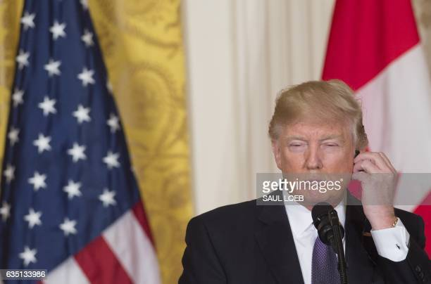 US President Donald Trump listens to an earpiece during a joint press conference with Canadian Prime Minister Justin Trudeau in the East Room of the...