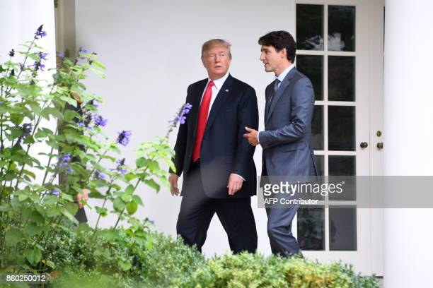 US President Donald Trump listens to Canadian Prime Minister Justin Trudeau as they walk towards the Oval Office of the White House in Washington DC...