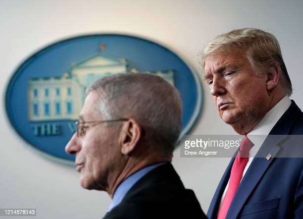 President Donald Trump, listens to Dr. Anthony Fauci, director of the National Institute of Allergy and Infectious Diseases, speak during a briefing...