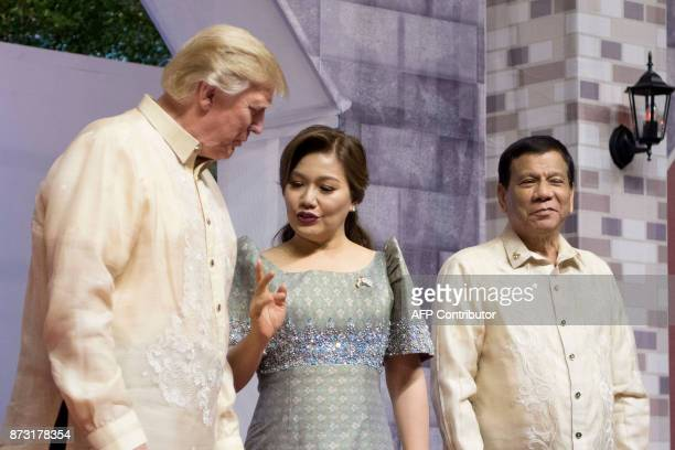 US President Donald Trump listens to Honeylet Avancena partner of Philippine President Rodrigo Duterte upon arriving for the special gala celebration...