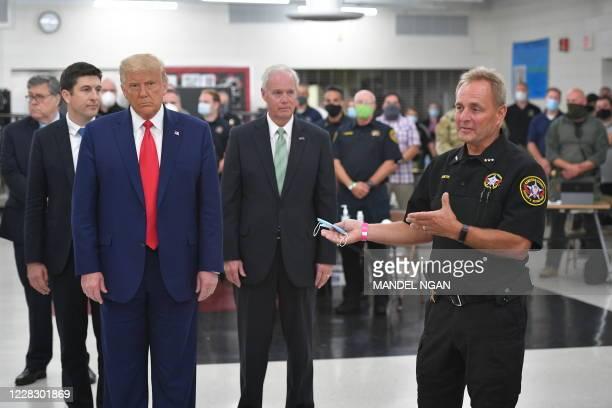 President Donald Trump listens to Kenosha County Sheriff David Beth on September 1 at Mary D. Bradford High School in Kenosha, Wisconsin. - Trump...