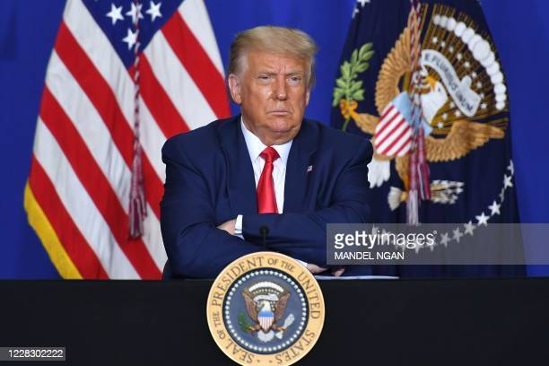 President Donald Trump listens to officials during a roundtable discussion on community safety, at Mary D. Bradford High School in in Kenosha,...