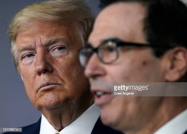 US President Donald Trump listens to Secretary of the Treasury Steven Mnuchin speak during a briefing about the coronavirus in the press briefing...