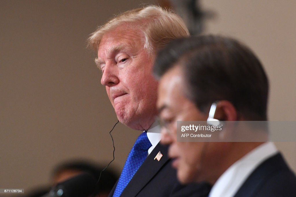 US President Donald Trump (L) listens to South Korea's President Moon Jae-In speak as they attend a joint press conference at the presidential Blue House in Seoul on November 7, 2017. US President Donald Trump arrived in Seoul on November 7 vowing to 'figure it all out' with his South Korean counterpart Moon Jae-In, despite the two allies' differences on how to deal with the nuclear-armed North. / AFP PHOTO / Jim WATSON