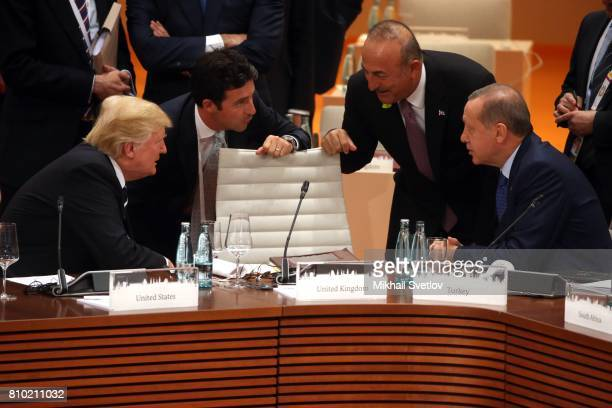 US President Donald Trump listens to Turkish Prime Minister Mevlut Cavusoglu as Turkish President Recep Tayyip Erdogan looks on Chinese President Xi...