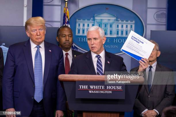 S President Donald Trump listens to Vice President Mike Pence speak during a briefing in the James Brady Press Briefing Room at the White House on...