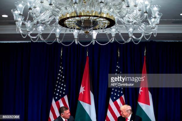 US President Donald Trump listens while Jordan's King Abdullah II makes a statement for the press before a meeting at the Palace Hotel during the...