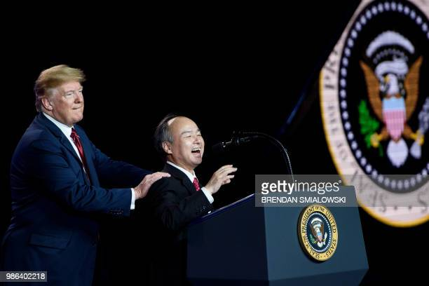 US President Donald Trump listens while Masayoshi Son Chief Executive Officer of SoftBank speaks at a Foxconn facility at the Wisconsin Valley...