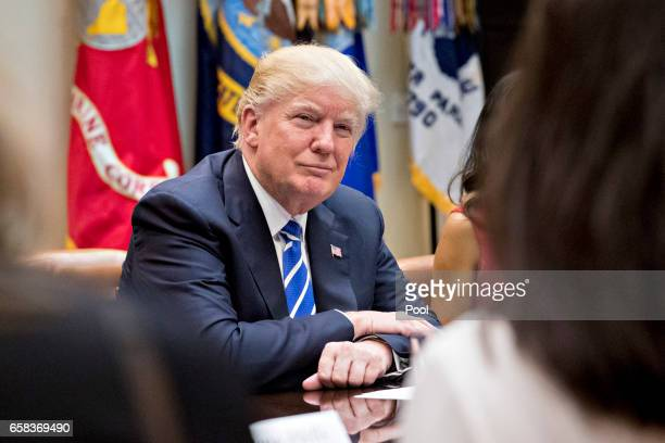 S President Donald Trump listens while meeting with women small business owners in the Roosevelt Room of the White House on March 27 2017 in...