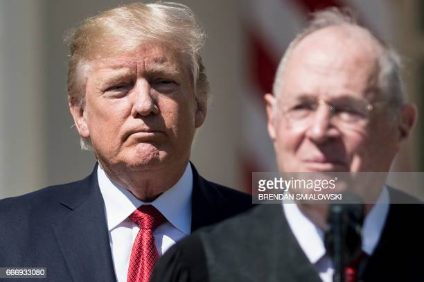 US President Donald Trump listens while Supreme Court Justice Anthony Kennedy speaks during a ceremony in the Rose Garden of the White House April 10...