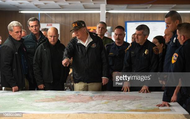 President Donald Trump looks at a fire incident map with Congressman Kevin McCarthy, and Gov. Jerry Brown, Gov.-elect Gavin Newsom during his visit...
