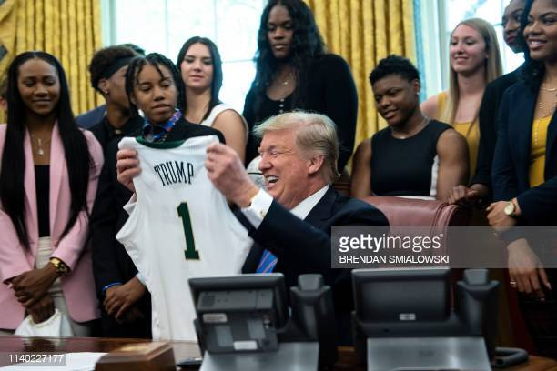 President Donald Trump looks at a jersey after being given it by the 2019 NCAA Division I champions from Baylor University's women's basketball team...