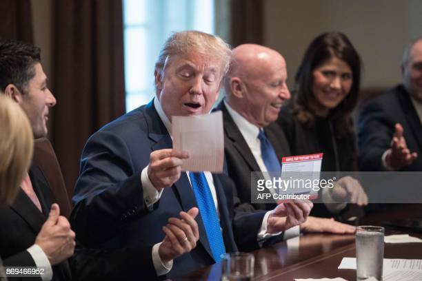 US President Donald Trump looks at a sample of the proposed new tax form as he meets with House Republican leaders and Republican members of the...