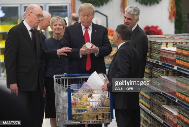 US President Donald Trump looks at an item as he pushes a shopping cart touring the Church of Jesus Christ of LatterDay Saints' food distribution...