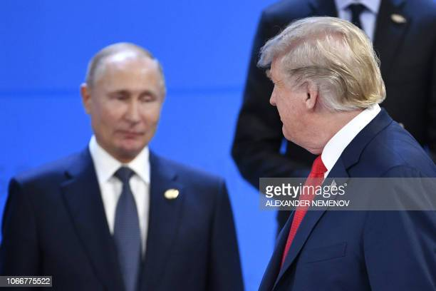 US President Donald Trump looks at Russia's President Vladimir Putin as they take their places for a family photo during the G20 Leaders' Summit in...