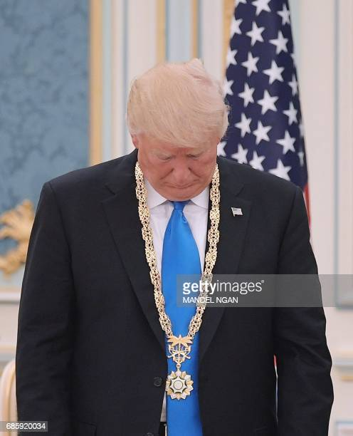President Donald Trump looks at the Order of Abdulla alSaud medal which he received from Saudi Arabia's King Salman bin Abdulaziz alSaud at the Saudi...