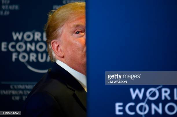 President Donald Trump looks back as a question from the press is shouted after a press conference at the World Economic Forum in Davos Switzerland...