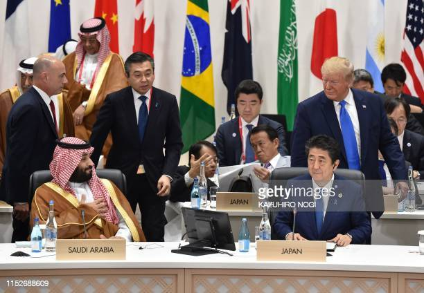 US President Donald Trump looks back at Saudi Arabia's crown prince Mohammed Bin Salman as he attends session 3 on women's workforce participation...