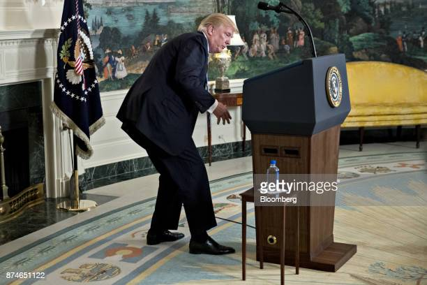 US President Donald Trump looks for a water bottle while delivering remarks on his recent 11day Asia trip in the Diplomatic Room of the White House...