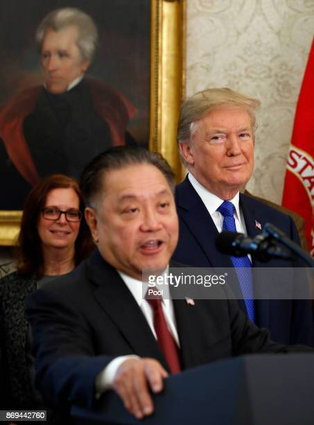 US President Donald Trump looks on as Broadcom CEO Hock Tan announces the repatriation of his company's headquarters to the United States from...