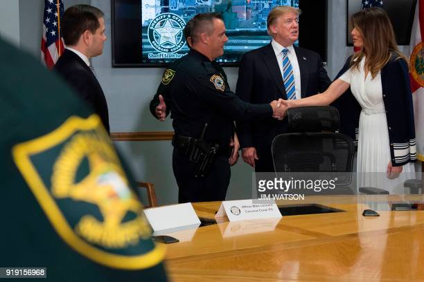 US President Donald Trump looks on as First Lady Melania Trump shakes hands with Coconut Creek Police Office Mike Leonard who arrested Florida...