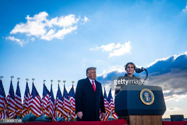 President Donald Trump looks on as First Lady Melania Trump speaks to supporters at Joint Base Andrews before boarding Air Force One for his last...