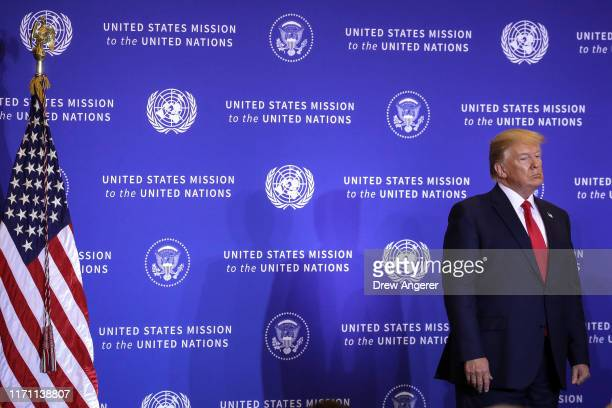 President Donald Trump looks on as Secretary of State Mike Pompeo speaks during a press conference on the sidelines of the United Nations General...