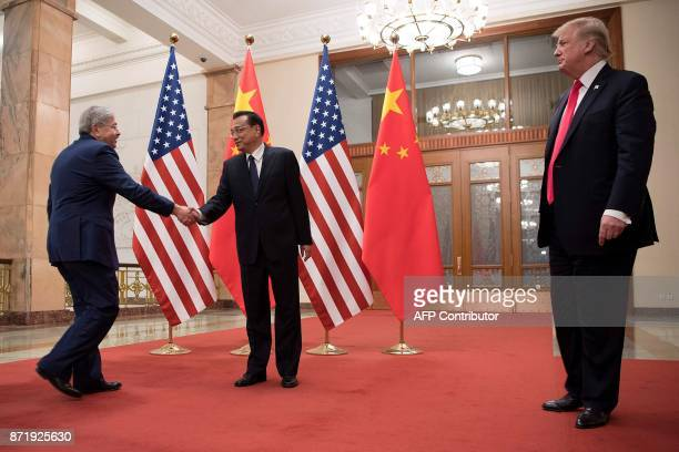 US President Donald Trump looks on as US Ambassador to China Terry Branstad shakes hands with China's Premier Li Keqiang in Beijing on November 9...
