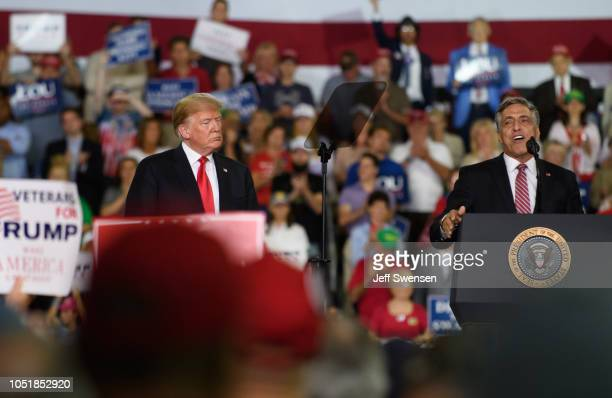 S President Donald Trump looks on as US Senate Republican candidate Lou Barletta speaks at a rally at the Erie Insurance Arena on October 10 2018 in...