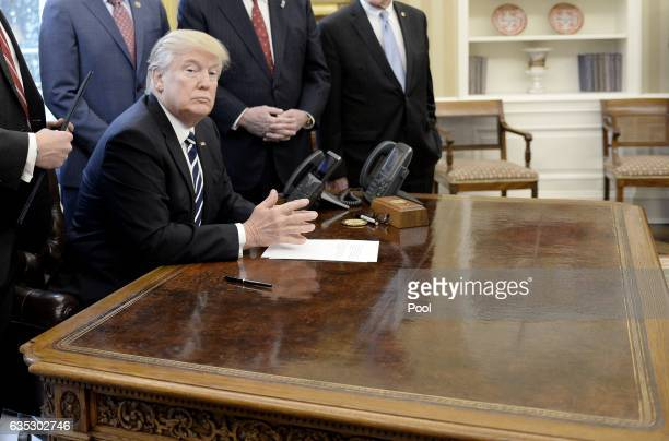 US President Donald Trump looks on before signing HJ Res 41 in the Oval Office of the White House on February 14 2017 in Washington DC The resolution...