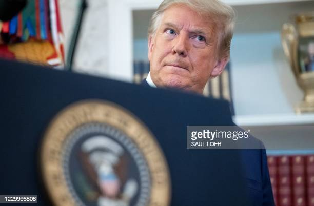 President Donald Trump looks on during a ceremony presenting the Presidential Medal of Freedom to wrestler Dan Gable in the Oval Office of the White...