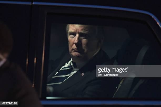 US President Donald Trump looks on from the presidential limo nicknamed The Beast following his arrival at Hanoi's Noi Bai airport on November 11...