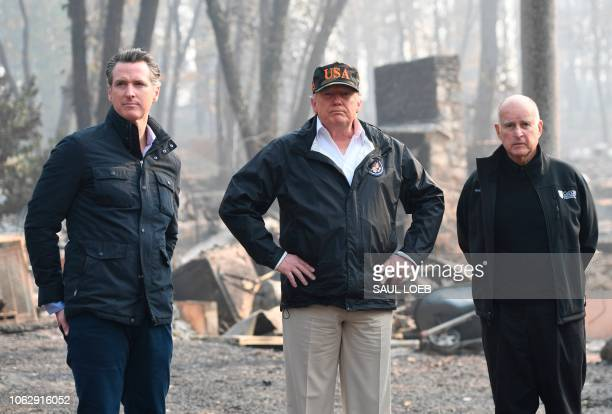 US President Donald Trump looks on with Governor of California Jerry Brown and Lieutenant Governor of California Gavin Newsom as they view damage...